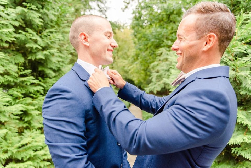 groom's tie adjusted by groomsman photographed by Renee Nicolo Photography