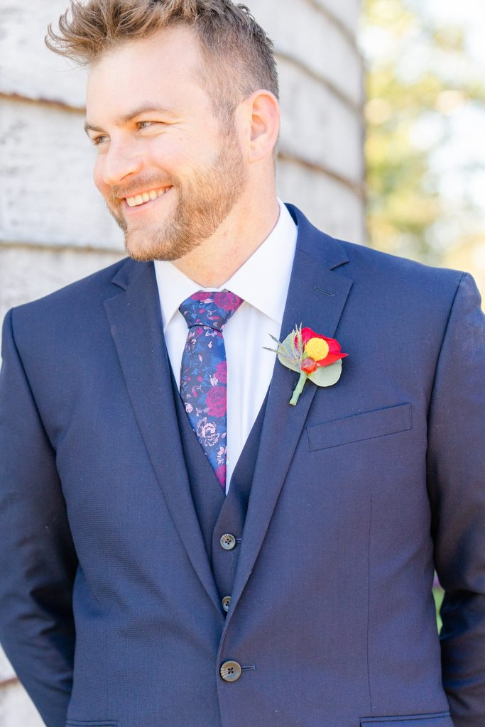 navy suit with fall floral boutonnière photographed by Renee Nicolo Photography