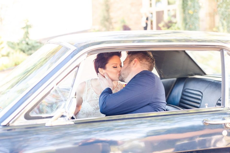 bride and groom pose in vintage car on wedding day with  Renee Nicolo Photography