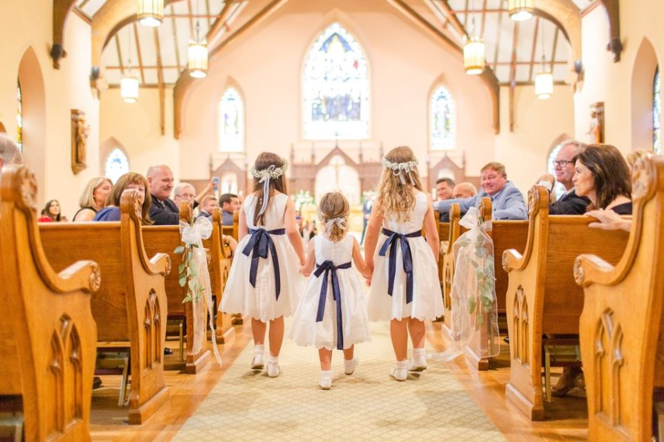 flower girls walk down aisle at church wedding with Renee Nicolo Photography