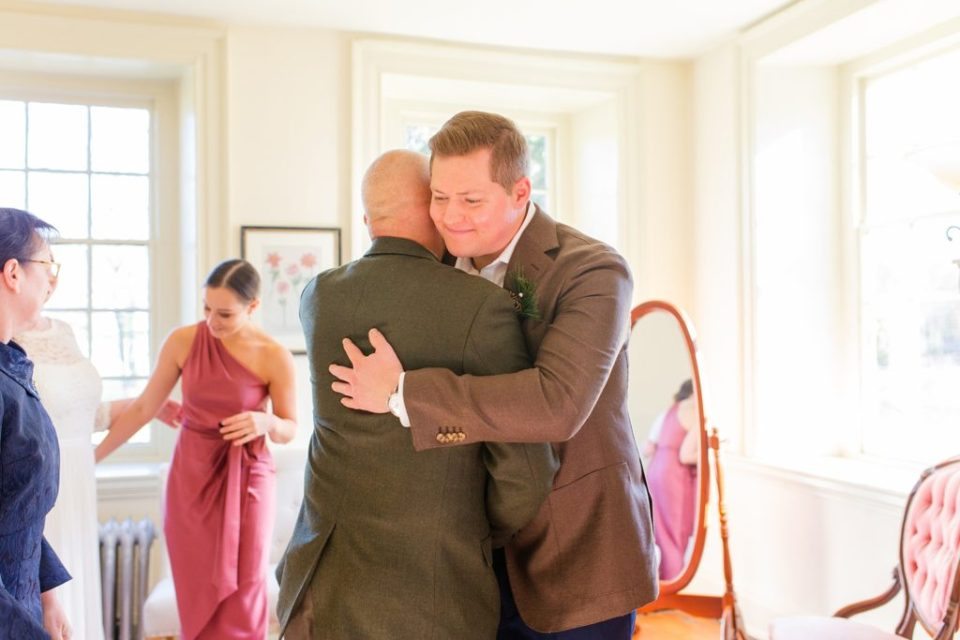 groom hugs father of bride photographed by Renee Nicolo Photography