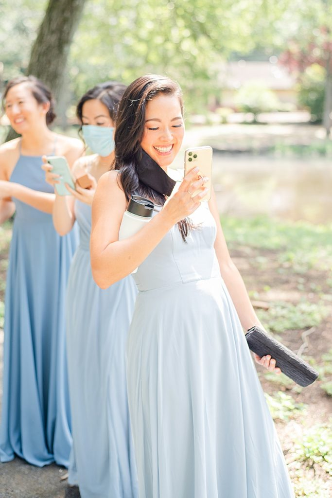 bridesmaid takes a photo of newlyweds meeting for first look
