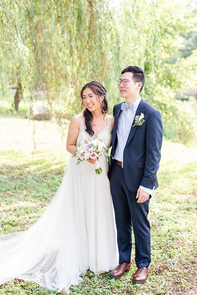 bride and groom smile during portraits before NJ backyard wedding