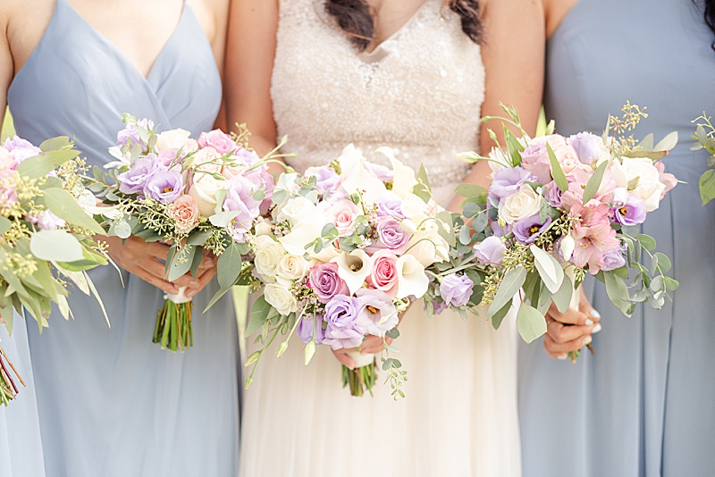 bride and bridesmaids hold pastel wedding bouquets
