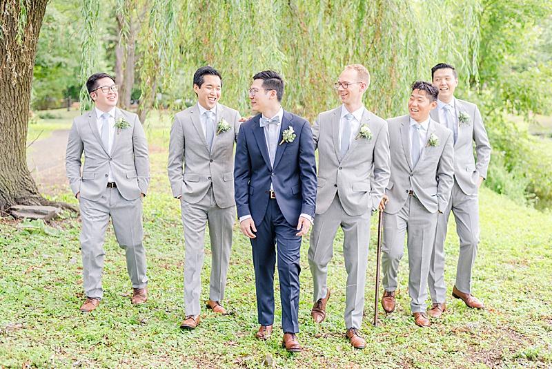 groom walks with groomsmen at Cooper Pond Park