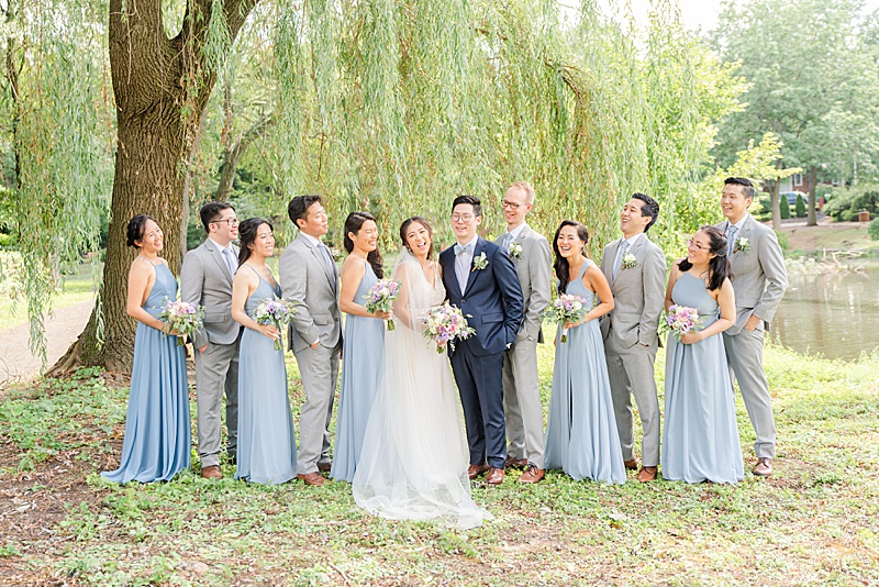 bridal party poses with bride and groom under willow tree