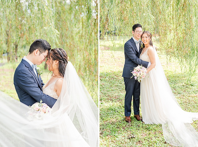 bride and groom pose by willow tree with veil flowing