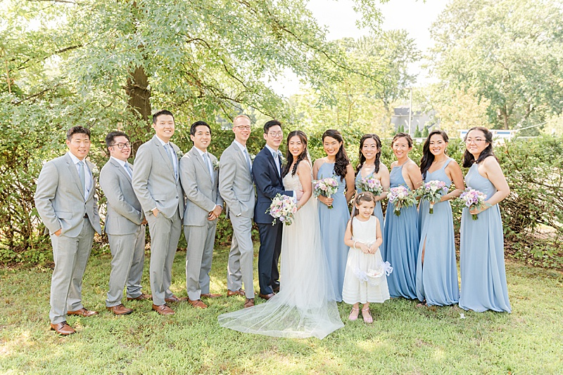 bridal party in dusty blue gowns and grey suits pose with bride and groom