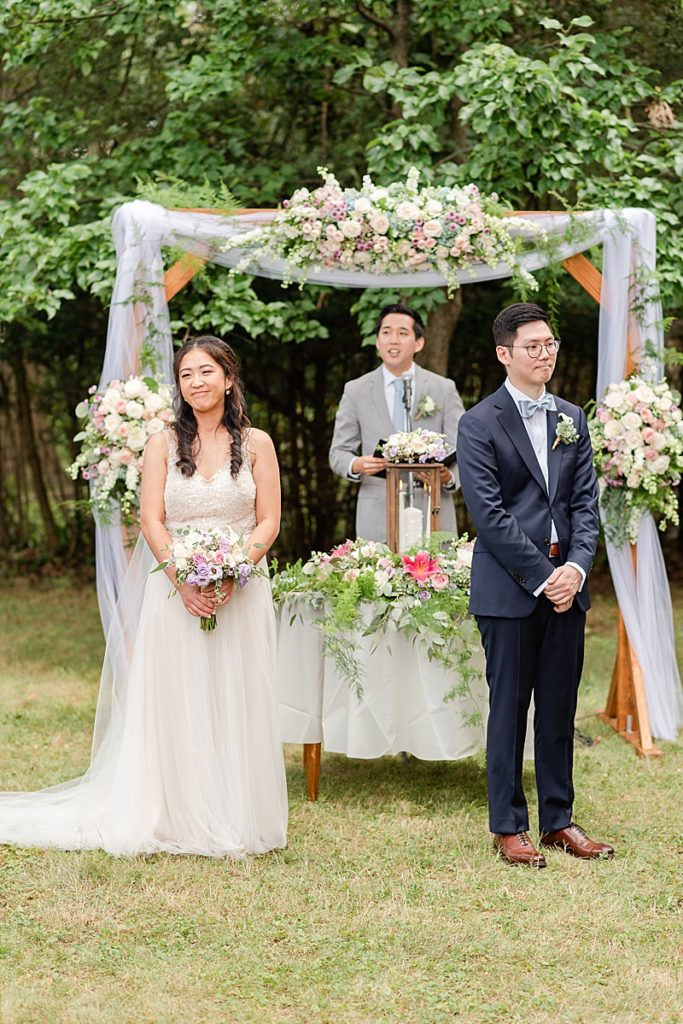 bride and groom welcome guests to NJ backyard wedding ceremony