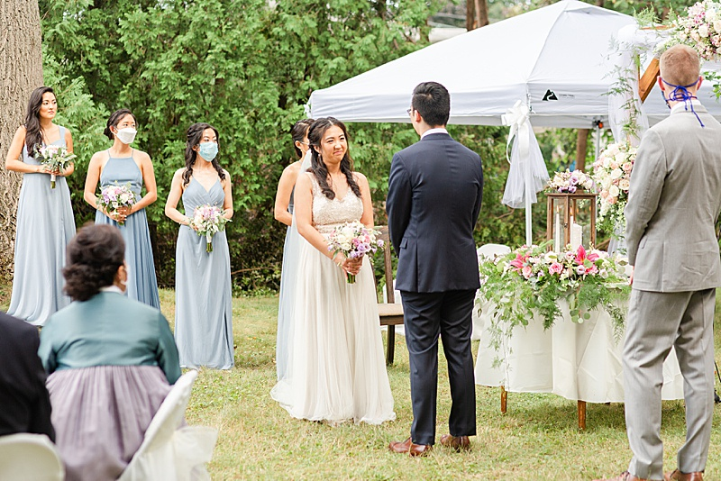 bride and groom smile during ceremony at each other