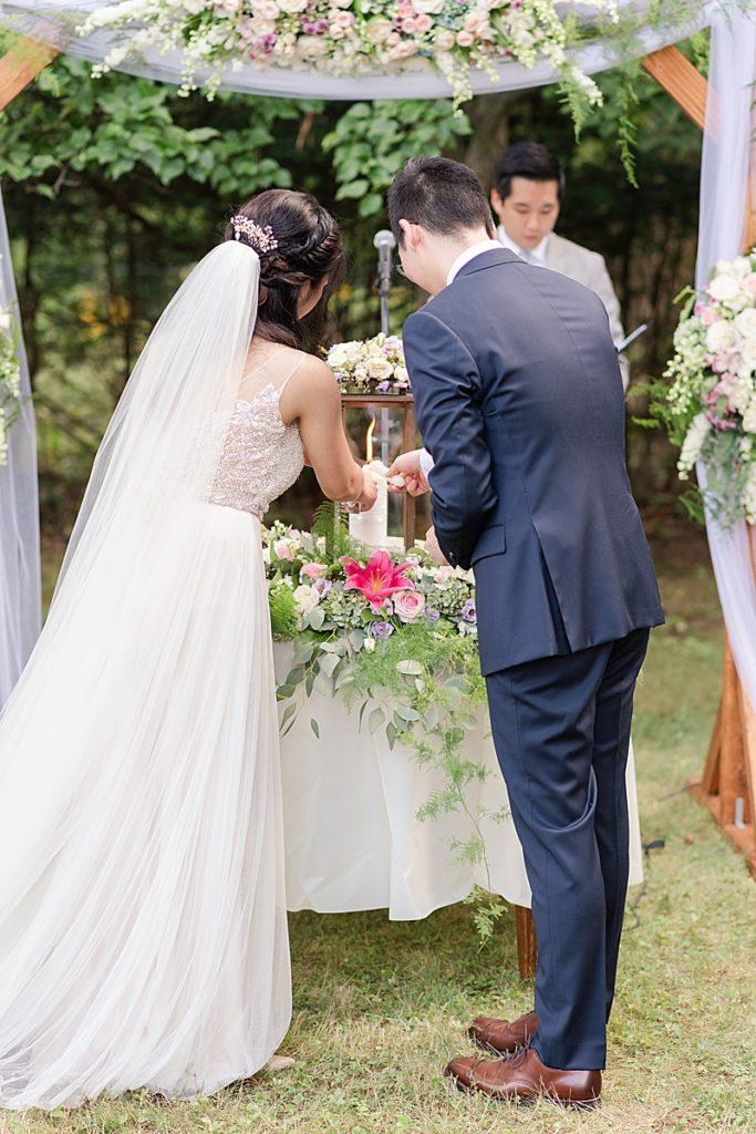 bride and groom light unity candle during NJ backyard wedding ceremony