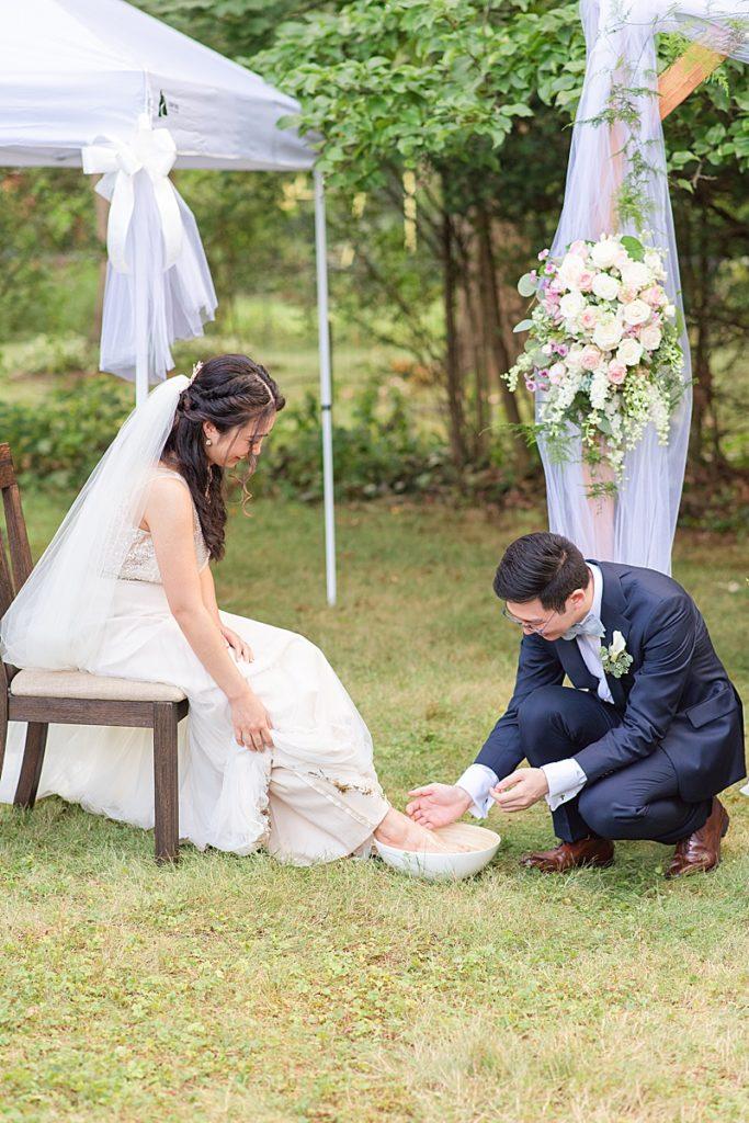 groom washes bride's feet during NJ backyard wedding ceremony