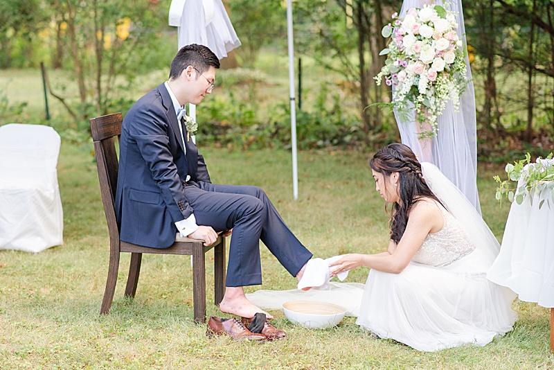 bride washes groom's feet during NJ backyard wedding ceremony