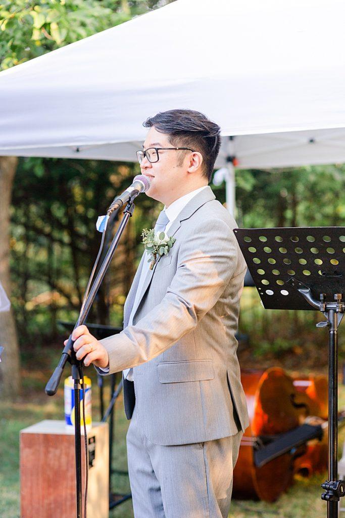 groomsman gives toast for bride and groom during NJ backyard wedding