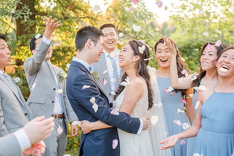 bridal party throws petals around newlyweds