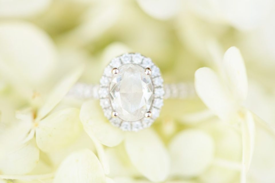 oval diamond ring rests on yellow flowers