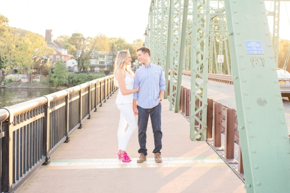 bride in white outfit with bright pink shoes holds onto groom