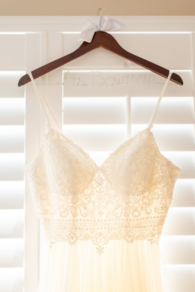 bride's dress with lace details hangs in bridal suite
