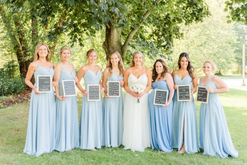 bride poses with bridesmaids in blue gowns holding signs with how they know bride
