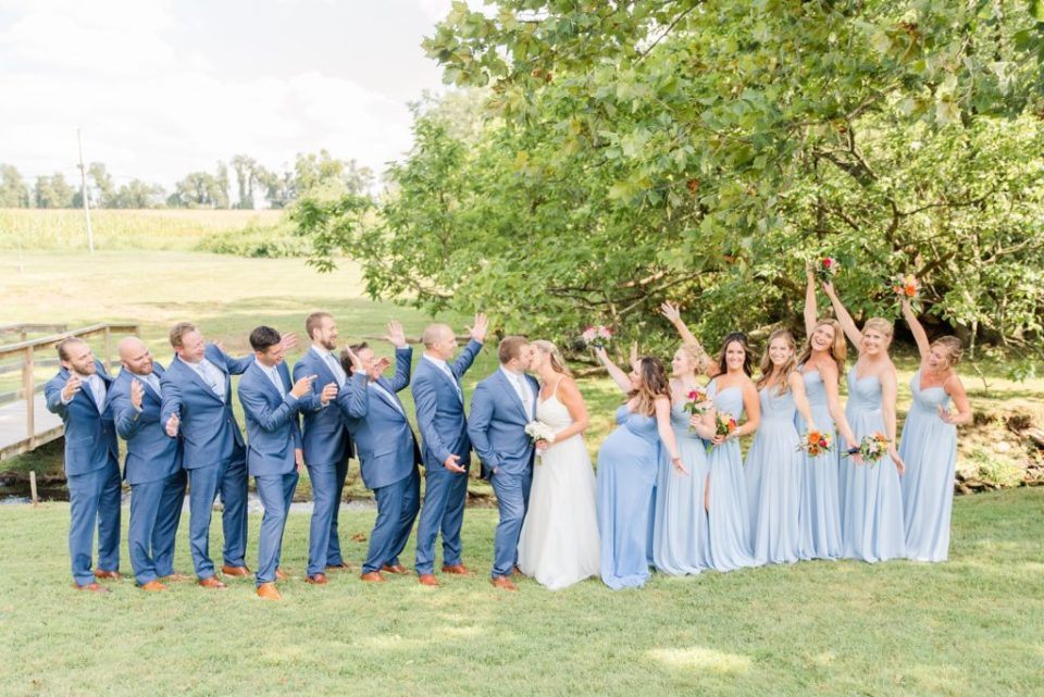 bridal party cheers while bride and groom kiss