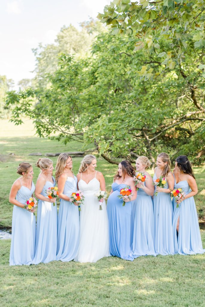 bridesmaids in blue dresses pose with bride