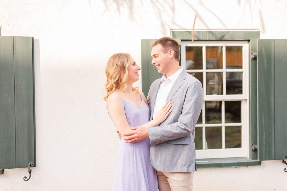 engaged couple poses in front of house with green shutters