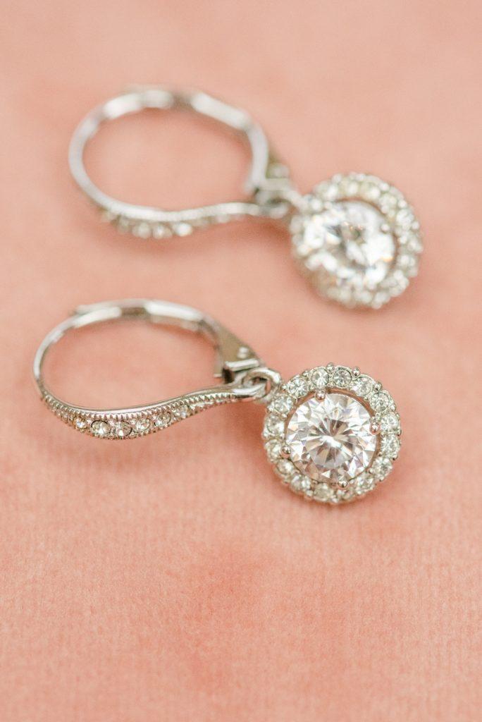 bride's earrings rest on pink backdrop