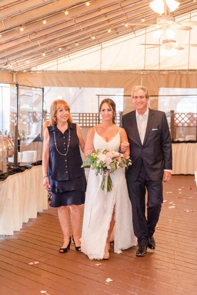 bride walks down aisle with parents