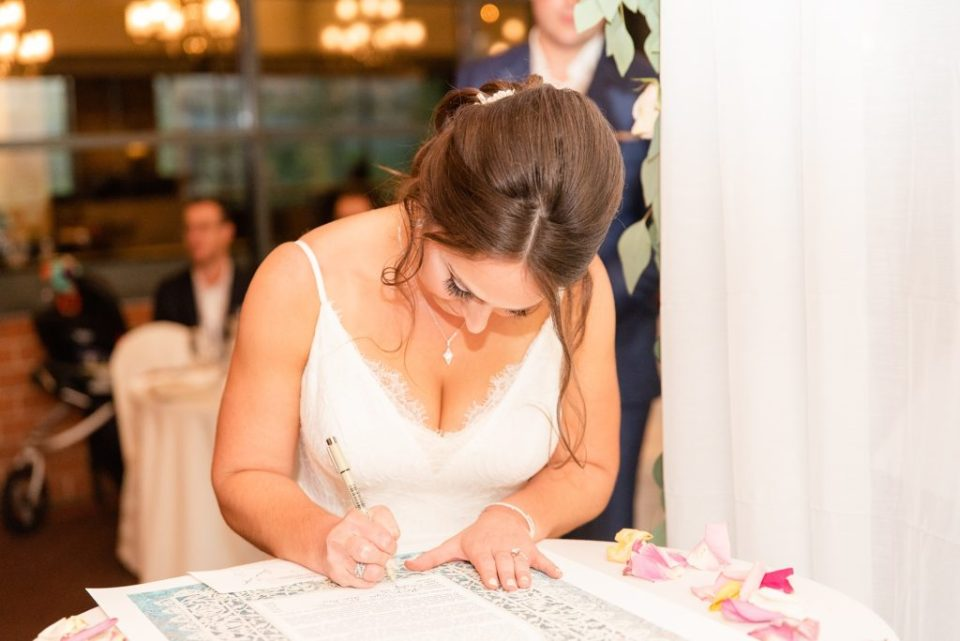 bride signs marriage agreement in Jewish ceremony