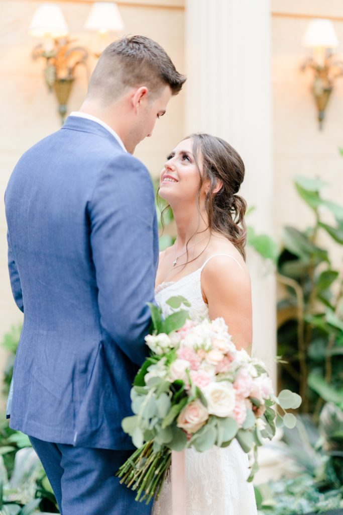 bride looks up at groom during wedding photos in hotel lobby