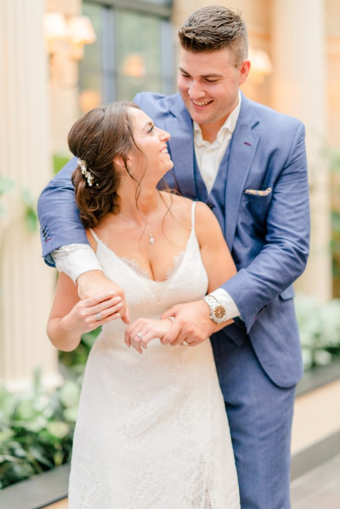 groom hugs bride from behind during Chest County PA wedding portraits