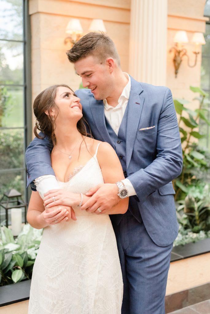groom hugs bride laughing during wedding photos