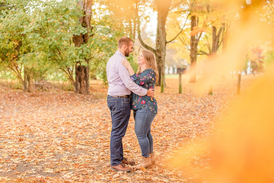 bride and groom look at each other during fall engagement photos