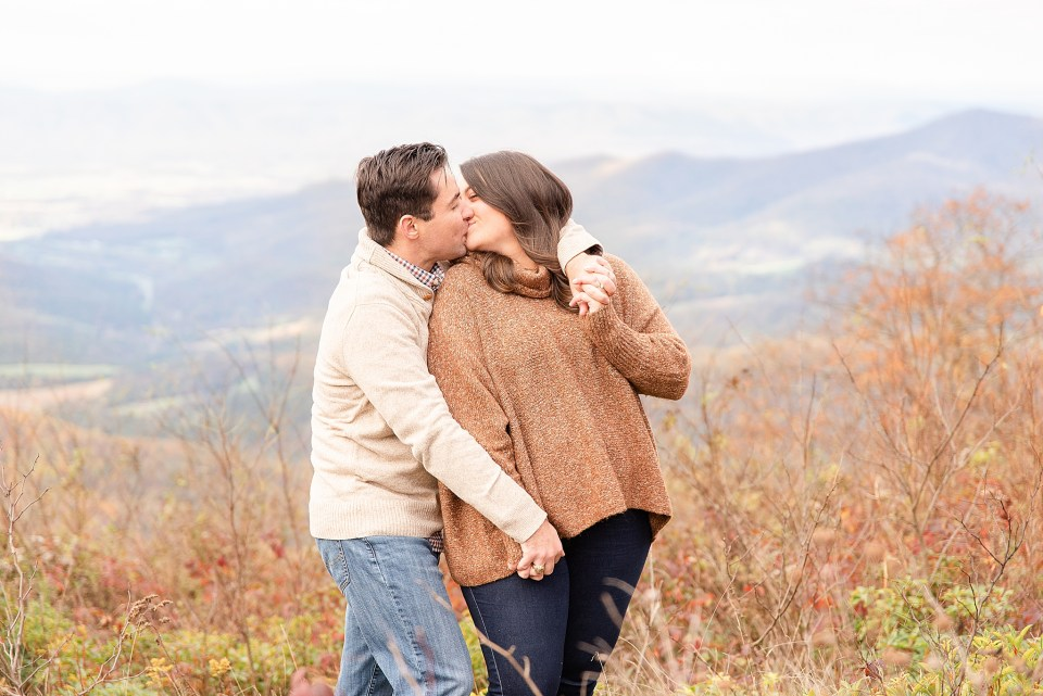 bride and groom kiss during engagement photos on mountain