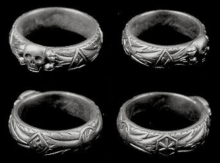 The SS Totenkopfring - Death's Head Ring Produced in silver, the Ring bore Runic Signs amidst oak leaves on the outside; the inside was engraved with the owner's name, the date he received the ring, and the signature of Reich Leader Of The SS Himmler.