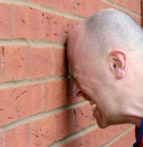 A man banging his head against the wall in frustration.