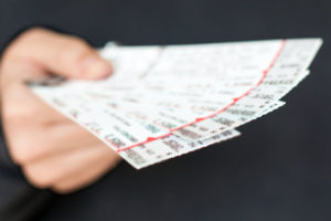 Tickets to a show / event in a hand with a black background. Photo credit: @iStock.com/GlasserStudios