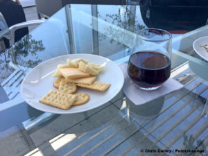 Cheese, crackers, and Camelot red wine are seen atop a glass table on the deck of the United Club LAX airport lounge in Los Angeles, California. © Chris Carley / PointsLounge.