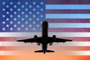 Airplane on sunset sky with American flag - USA travel concept. (Photo: ©iStock.com/hanohiki)
