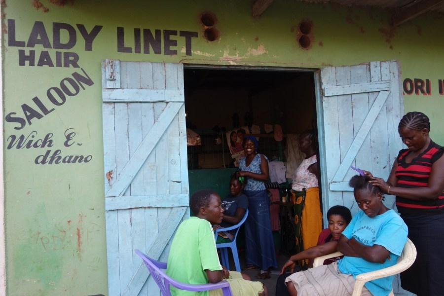 Linet braids a customer's hair.