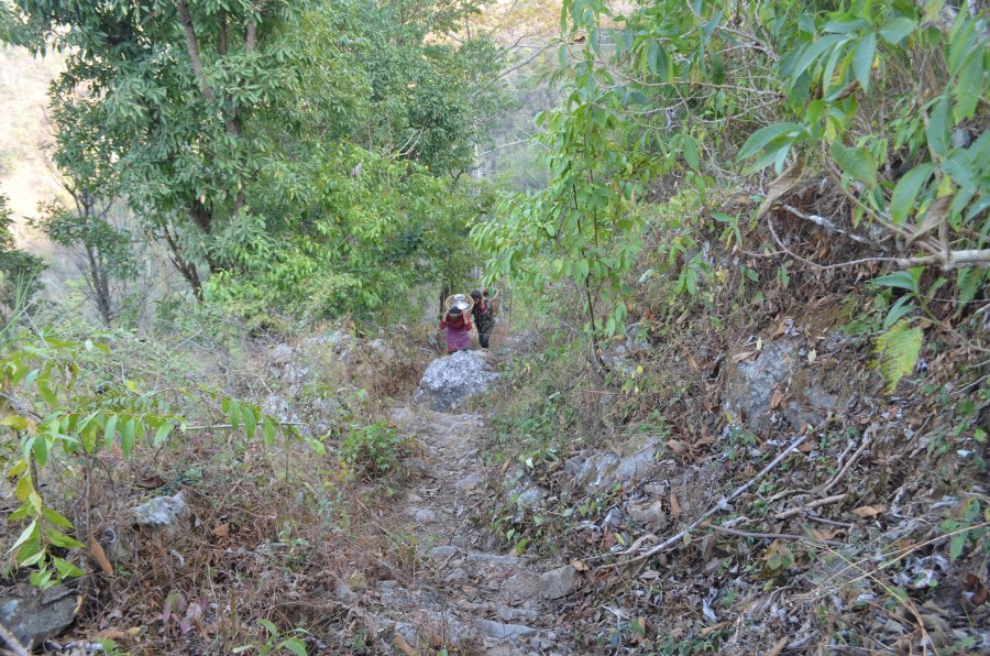 Looking down a steep hill path with two women climbing up carrying heavy loads of water on their backs