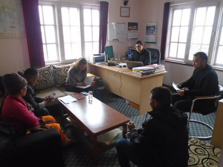 The photo shows a meeting between  Renewable World representatives, community representatives, and the Local NGO. Six individuals sitting in an office, one lady is taking ones.
