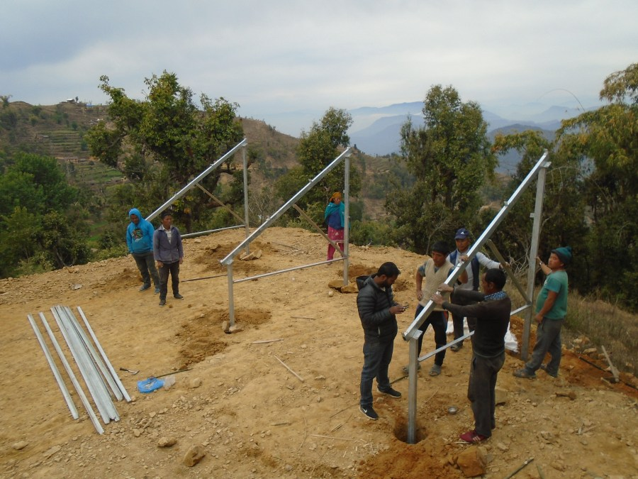 A metal frame, consisting of three triangular pieces, being erected on the hillside in Nepal with a eight community members inspecting the work