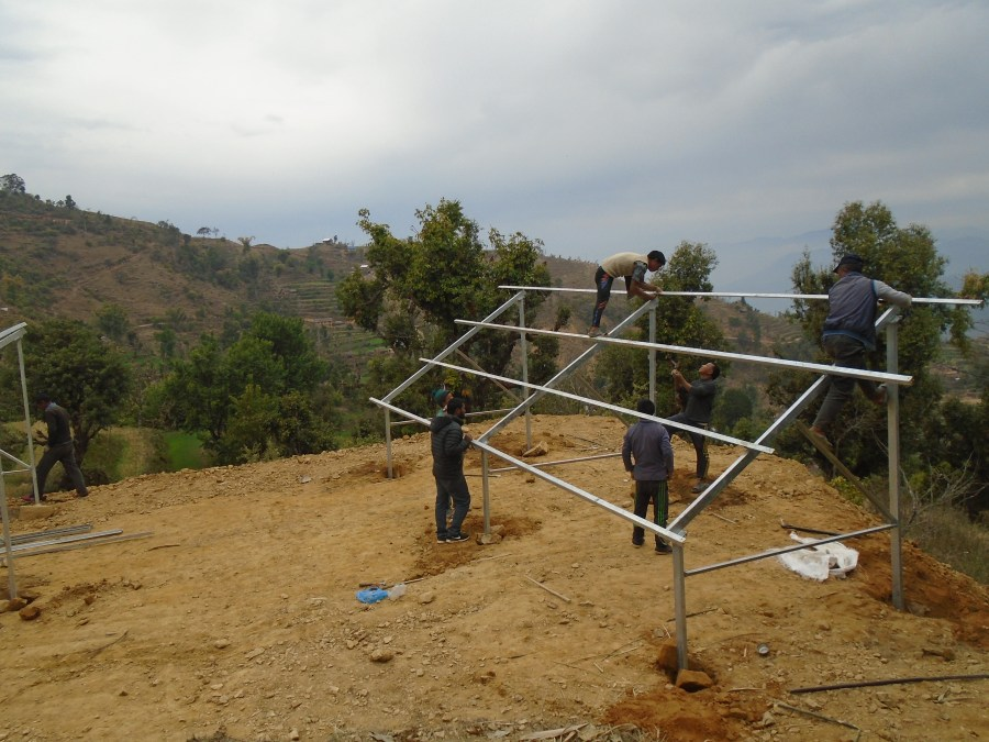 Solar panel frame fully erected with community members observing