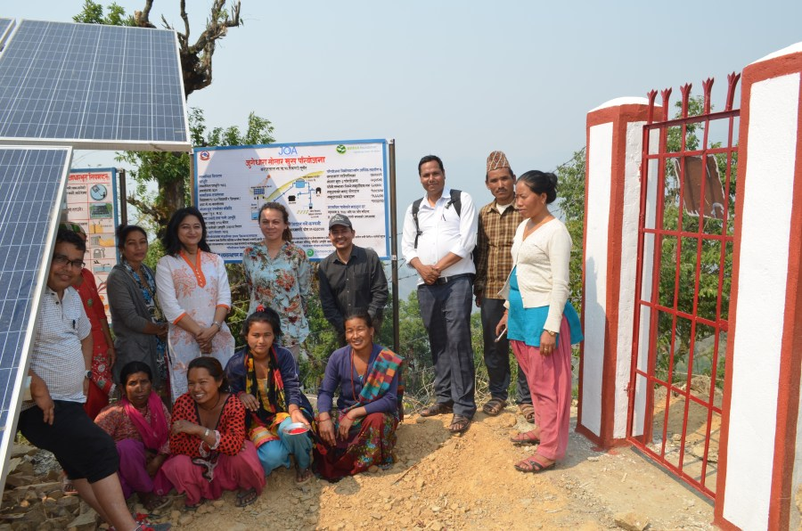 A group of community members smiling and standing next to the solar panels.