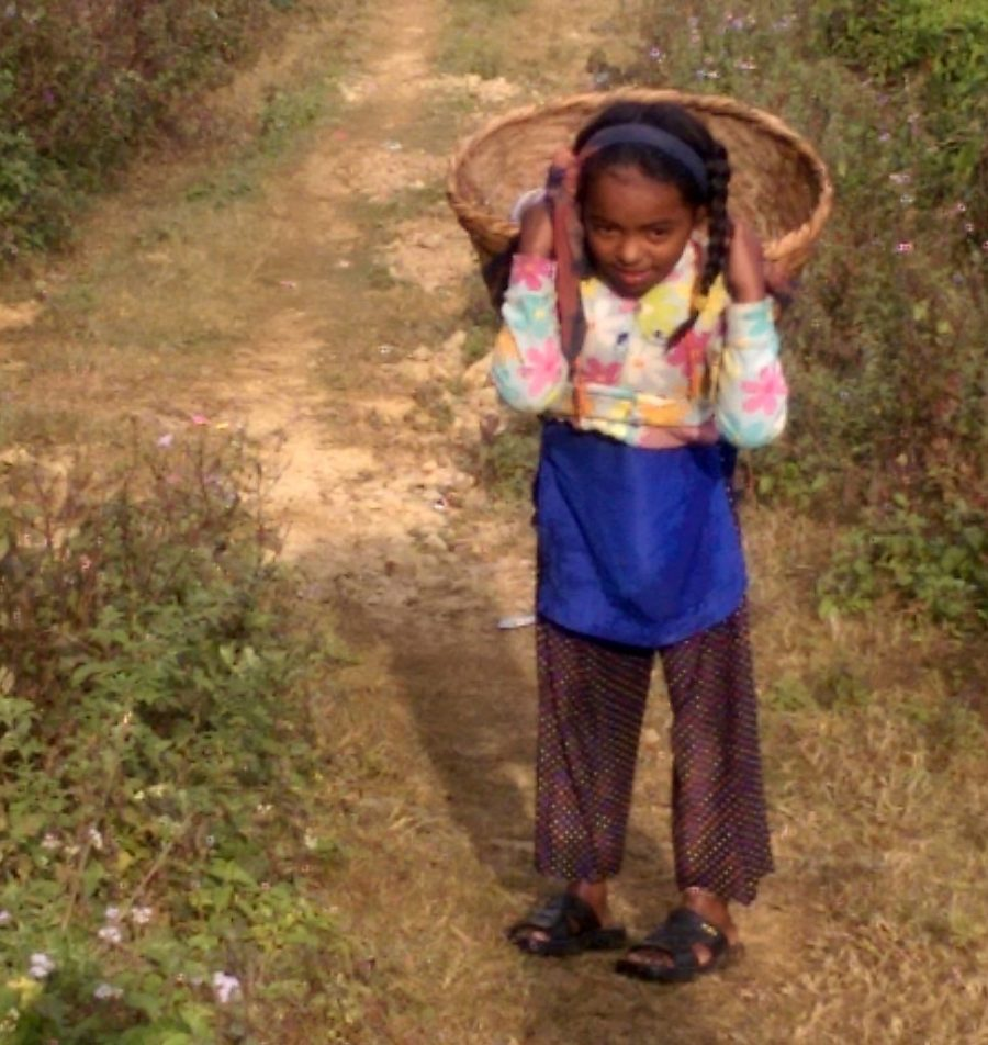 A Nepalese child carries water.