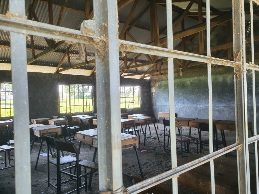 Looking through the window of a classroom at Markmatunga Secondary School on Kiwa Island. A bare room with basic chairs and tables, some broken, a dusty floor, a large chalk board on the wall, and two electric lighbulbs fitted to the ceiling powered by the solar microgrid installed on Kiwa Island