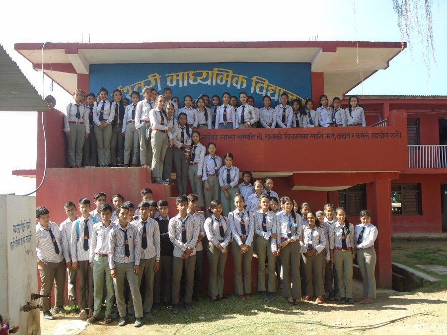 Students of the Ishwori Secondary School line up for a photograph in front of the school building.
