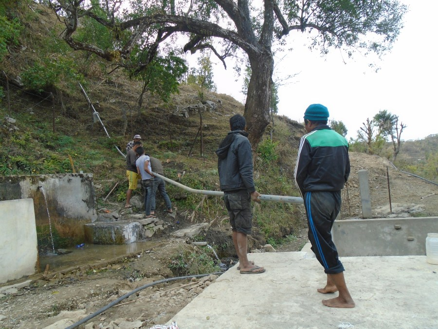 Community members work together on the piping which is taking place and installed on a hill in Jugedhara.