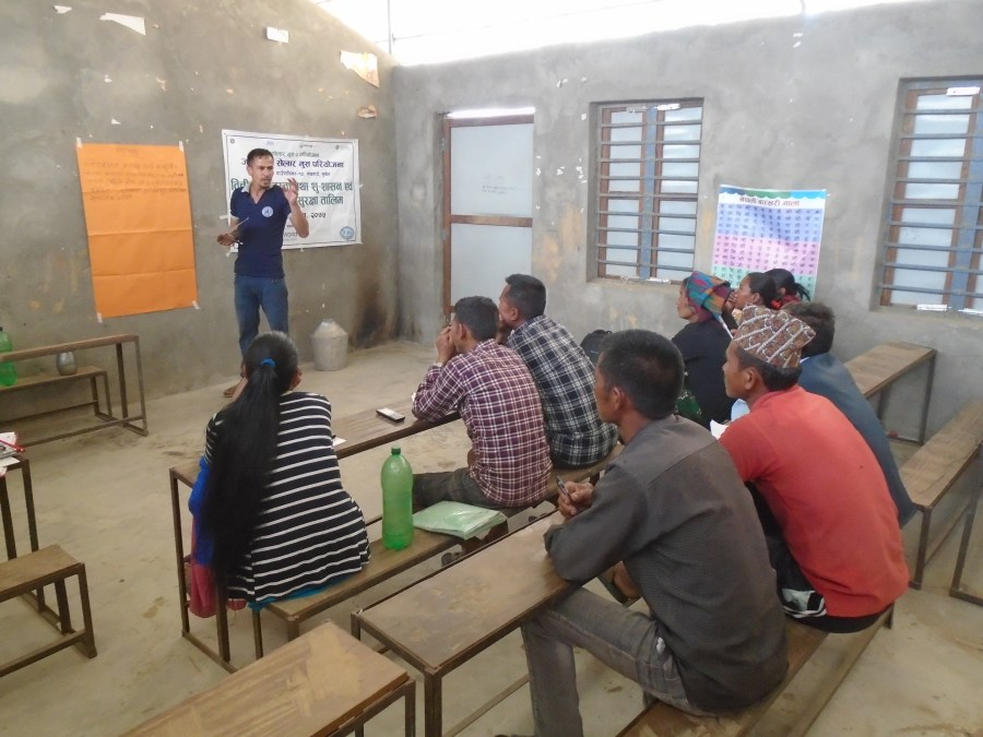 Training on water resource management and health and safety, led by a project worker, with many community members.